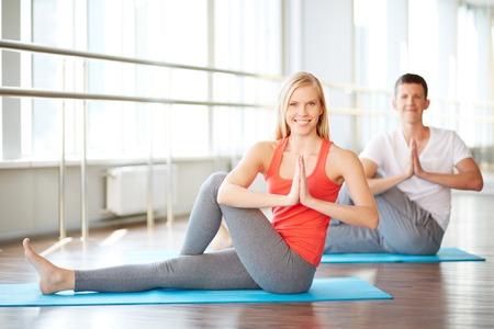 Young couple doing yoga exercises in fitness club photo