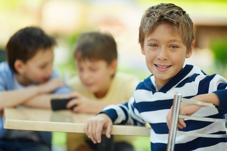 Portrait of smiling boy in cafe with his friends in the background Stock Photo