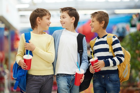 children walking: Three carefree schoolboys talking after studies Stock Photo