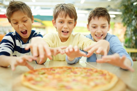Three funny boys eating pizza in cafe  Stock Photo