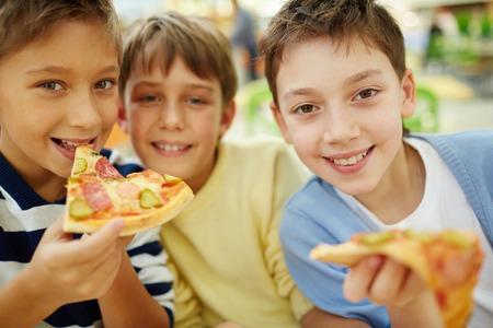 kid eat: Three happy boys enjoying pizza Stock Photo