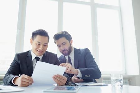 contrato de trabajo: Dos gerentes discusiones sobre el contrato en la sala de reuniones