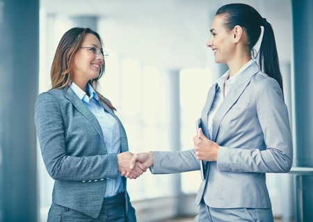 handshaking: Image of two confident businesswomen handshaking