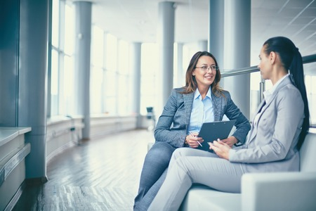 Image of two friendly businesswomen sitting and discussing new ideas