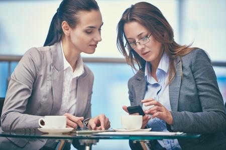 amigas conversando: Imagen de dos mujeres de negocios amigable utilizando tecnologías modernas en la oficina