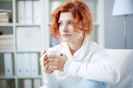 worried woman: Portrait of a worried woman with cup of tea