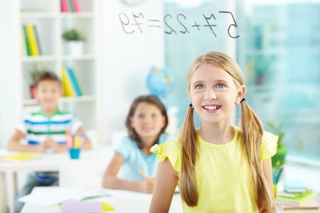 sumas: Retrato de ni�a bonita mirando sumas a bordo transparente con compa�eros de escuela en el fondo