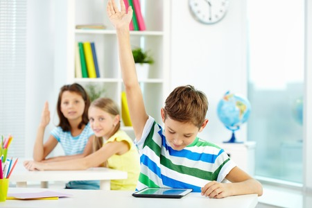 Portrait of smart lad at workplace raising hand and looking at touchpad with his classmates on background Stock Photo