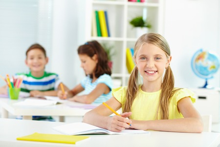 Lovely girl looking at camera with smile during lesson photo