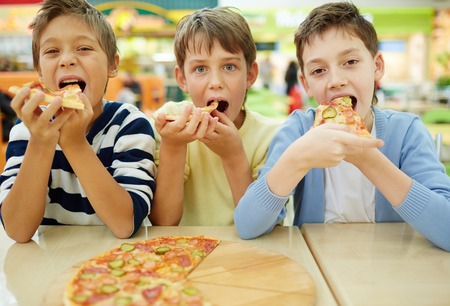 Three little boys eating pizza at cafe  Stock Photo