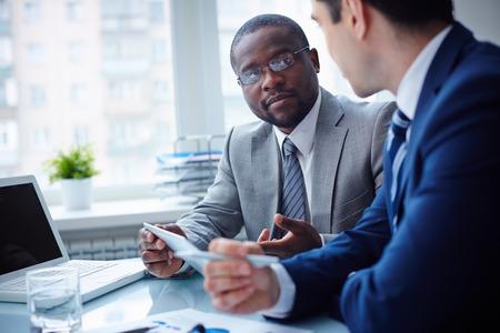 オフィスでの会議に相互に作用する 2 人の若いビジネスマンのイメージ