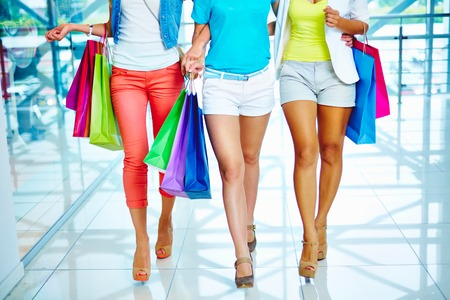 personal shopper: Legs of three glamorous girlfriends with paperbags walking down trade center Stock Photo