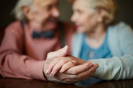 Close-up van senior vrouwelijke hand in die van haar echtgenoot