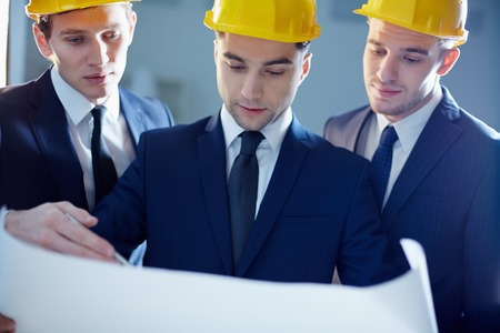 Close-up of workers looking at blue print and planning  photo