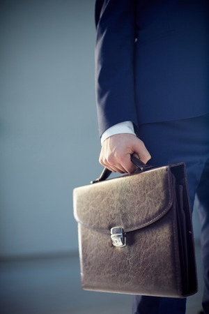 Vertical cropped image of a businessperson carrying a leather briefcase isolated on grey  photo