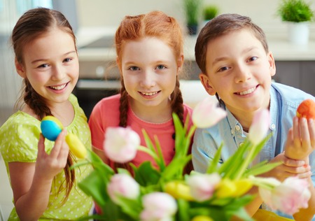 Portrait of three smiling children with Easter eggs photo