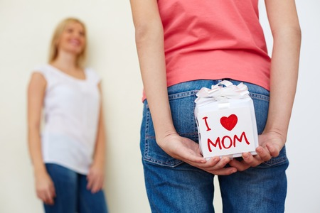 gift behind back: Close-up of teenage girl in jeans holding giftbox for mom behind her back Stock Photo