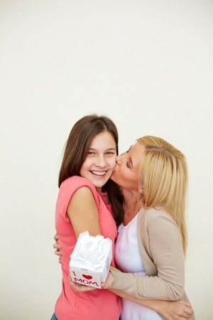 Thankful woman with small present kissing her daughter Stock Photo
