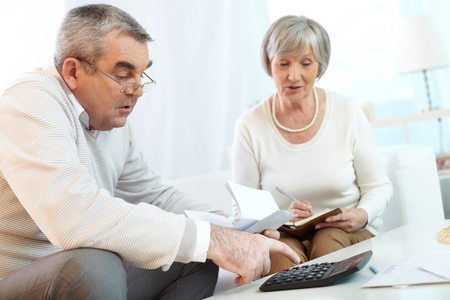 financial issues: Senior couple counting their expenses
