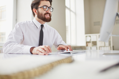 busy beard: Smiling businessman sitting in office and typing