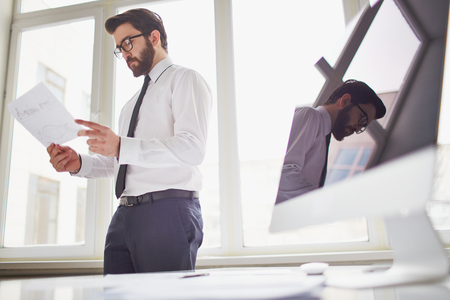 businessman standing: Young businessman standing by the window in office and looking at paper