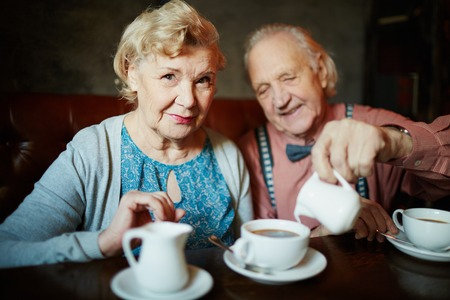 Portrait of retired couple in smart clothes having tea in cafe photo