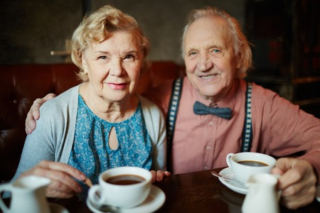 Portrait of retired couple in smart clothes looking at camera in cafe photo