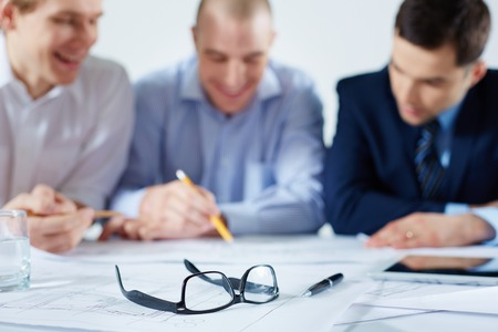 Closeup image of eyeglasses and a ballpoint on the table where business colleagues sharing the ideas on the foreground  photo