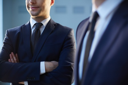 dress code: Cropped image of a confident businessman standing near his colleague on the foreground