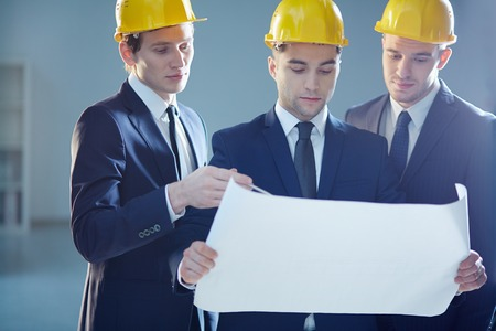 Closeup image of three constructors developing the business project  photo