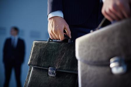 자신의 동료 배경에 서있는 동안 전경에 서류 가방을 들고 비즈니스 파트너 자른 이미지 스톡 콘텐츠