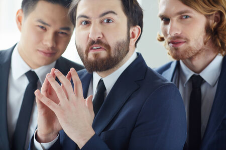 Annoyed businessman looking at camera with his colleagues on background Stock Photo