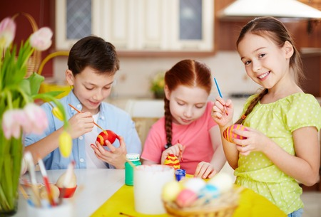 painting and decorating: Diligent pupils painting Easter eggs
