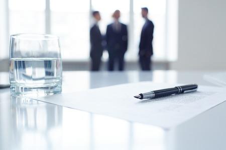 ビジネス ドキュメント、ペンおよび背景の仕事仲間のグループと職場での水のガラスのイメージ