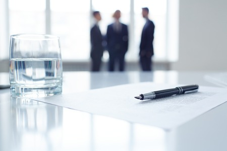 Imagen del documento de negocio, la pluma y el vaso de agua en el lugar de trabajo con un grupo de colegas en el fondo
