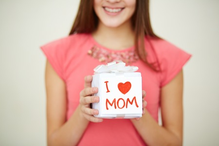 Close-up of teenage girl holding giftbox for mom photo