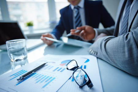 Image of eyeglasses and financial documents at workplace with businessmen discussing ideas near by Stock Photo