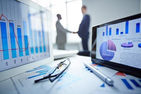 Afbeelding van een bril, pen, twee touchpads en financiële documenten op de werkplek met zakenlieden handshaking op de achtergrond Stockfoto