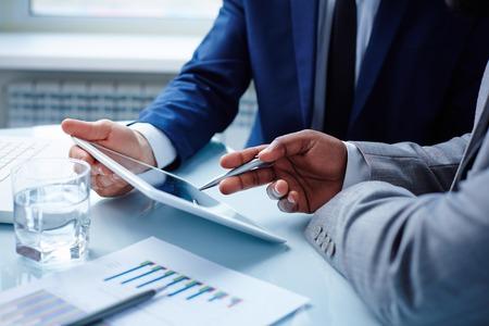 データ会議でタッチパッドで議論するビジネスマンのイメージ
