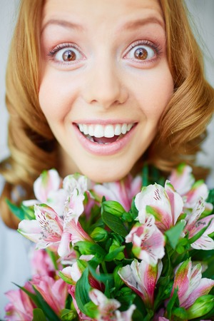 occasion: Portrait of surprised female with bunch of pink lilies