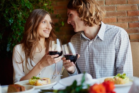 toasting wine: Portrait of amorous young couple toasting with red wine