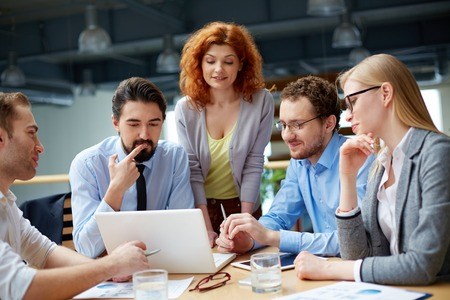 비즈니스 파트너 그룹 회의에서 노트북에 데이터를주의 깊게보고