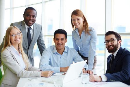 Compañía de cinco empleados que se sientan en el lugar de trabajo en la oficina Foto de archivo - 26806409