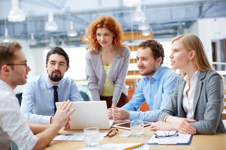 Groep van zakelijke partners kijken naar de jonge man die computer project tijdens de vergadering