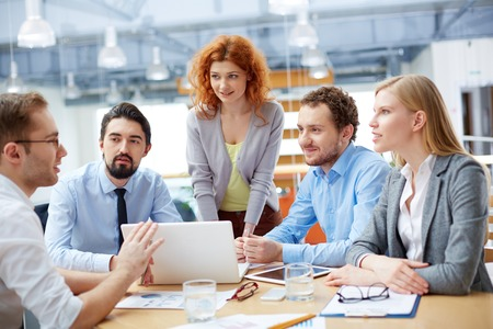 female executive: Group of business partners looking at young man presenting computer project at meeting
