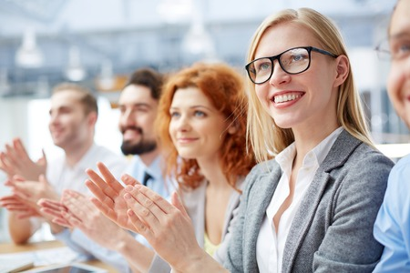 people clapping: Group of happy business people applauding at conference with smiling blonde in front Stock Photo