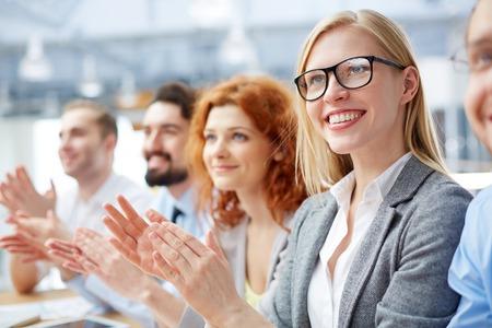 manos aplaudiendo: Grupo de gente de negocios feliz aplaudiendo en una conferencia con rubia sonriente delante