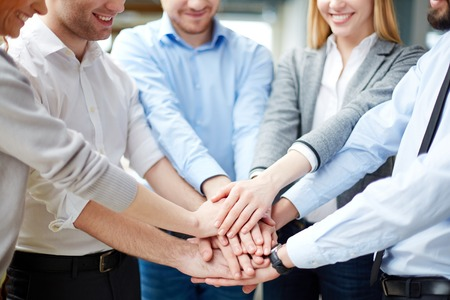Arms of business partners keeping their hands on top of each other symbolizing teamwork photo