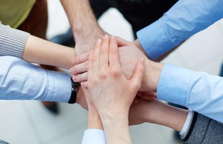 compa�erismo: Socios de negocios de las manos una encima de la otra compa��a que simboliza Foto de archivo