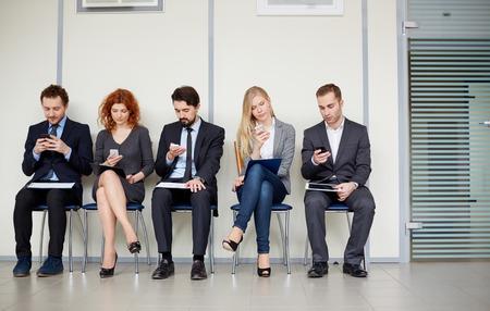 Fila de varios socios de negocios que utilizan sus teléfonos móviles Foto de archivo - 26806491